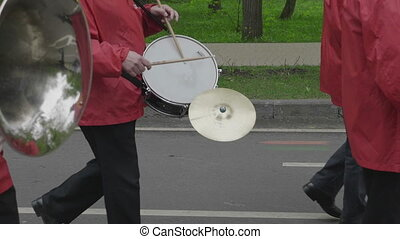 Street musicians go and play on the drum and trumpet