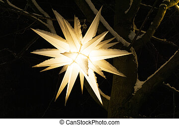 Street New Year and Christmas decorations. Decorative, winter festive lantern in the shape of a star on a Christmas tree for the celebration of Christmas is covered with snow