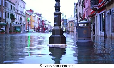 Street pillar and large trash can stand flooded with water after strong canal tides in famous small Italian Chioggia city