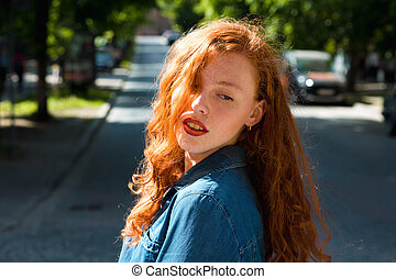 Street portrait of attractive red head woman in blue jeans shirt in rays of sun at the street