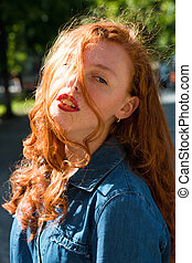 Street portrait of beautiful red head model in blue jeans shirt in rays of sun at the street