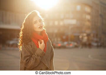 Street portrait of fabulous brunette model with wavy hair posing in soft evening backlight. Space for text