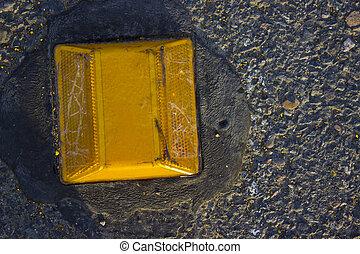 Street Reflector - A yellow street reflector on a black...