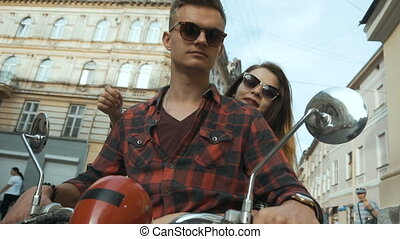 Young attractive couple of teenagers wears sunglasses riding retro motorbike, sunny street, urban hipster concept, 120FPS slowmotion
