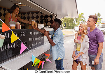 happy customers queue at food truck - street sale and people...