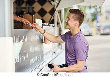 happy young man paying money at food truck