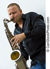 Street Sax Player - A street musician leaning against a...