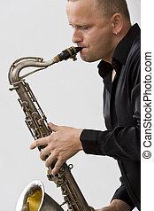Street Sax Player - A street musician leaning againsta white...