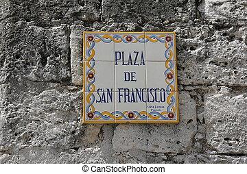 Street sign on a gray stone wall in Havana, Cuba