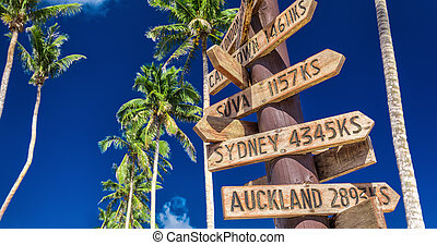 Street sign on the beach indicating directions to different places of the world, from Samoa