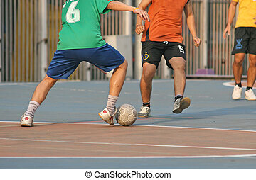 Player make a tackle in a game of street football (soccer)