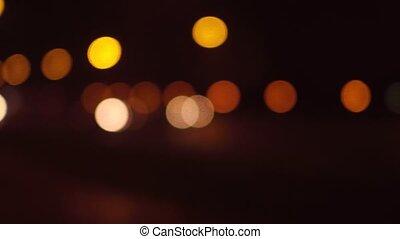 Street traffic bokeh circles at night. Cars passing by. 4K pan shot