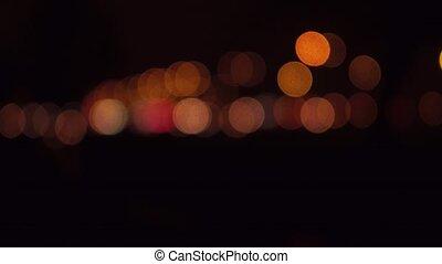 Street traffic bokeh circles at night. Cars passing by. 4K...