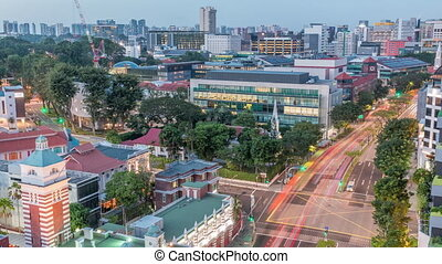 Street traffic on intersection near the fire station and skyline of Singapore day to night transition aerial timelapse. The Central Fire Station is the oldest existing fire station in Singapore on Hill street