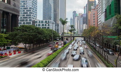 Street traffic with skyscrapers in Hong Kong at day time-lapse. pan up