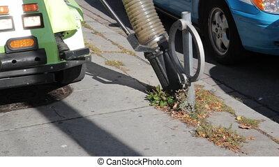 Street vacuum. - A vacuum cleaner%u2019s nozzle sucks up...