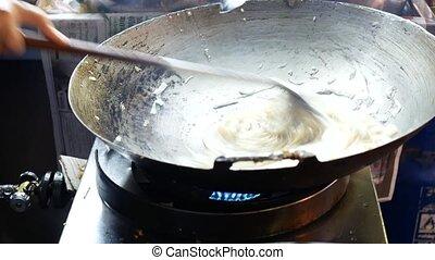 Street vendor cooking noodles at night market. 4k video footage.