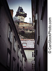 Street view looking up at the Graz clock tower in Austria