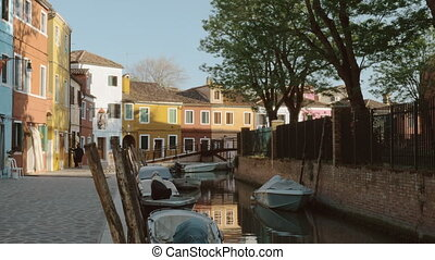 Street with canal and coloured houses in Burano island,...