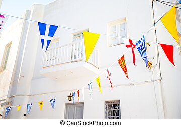 Street with colorful flags in Mykonos, Greece - Greek flags...