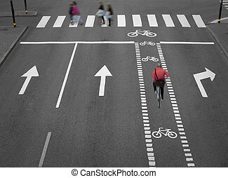 Blurred cyclist on empty street with arrows and a cycliing path