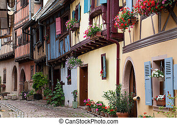Street with half-timbered medieval houses in Eguisheim ...