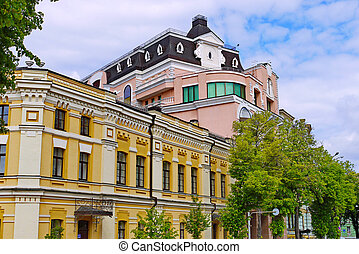 Street with several beautiful modern buildings against a blue sky with small white clouds