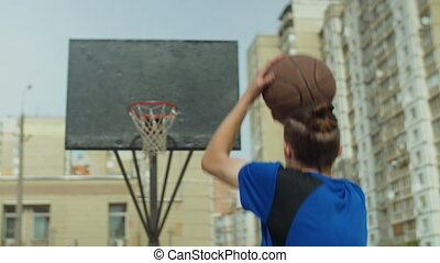 Streetball player failing to score after set shot - Rear...