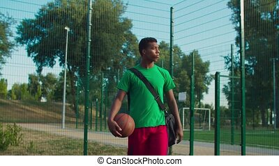 Concentrated handsome african street basketball player with gym bag bouncing ball , walking on outdoor court, ready to play match in early morning, expressing motivation and determination.