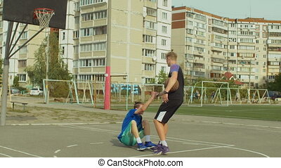 Streetball player helping fallen opponent to stand up -...