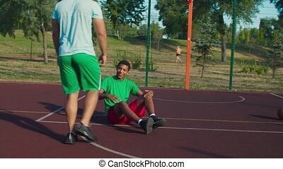 Sporty fit mixed race streetball player extending hand to lift fallen opponent player off ground, helping to stand up , practicing good sportsmanship during basketball game on outdoor court.