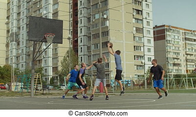 Sporty teenage streetball player making successful assist to teammate while playing game on basketball court. Basketball player passing ball and teammate scoring field goals during streetball match.