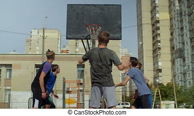 Streetball player taking a free throw on court - Rear view...