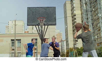 Streetball players figthing for rebound on court - Active...