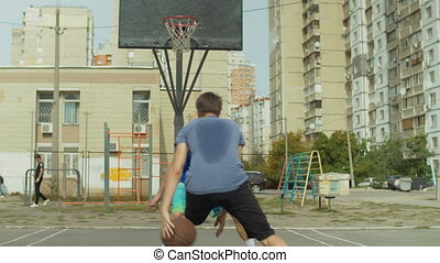 Streetball players in action on basketball court - Sporty...