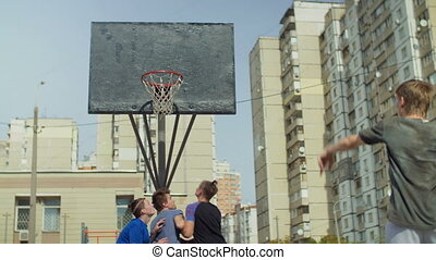 Streetball players jumping to take rebound on court -...