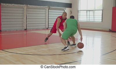 Two athletic african american streetball players in uniforms playing hart-court play on indoor basketball court. Black basketballers training individual skills, playing one on one game.