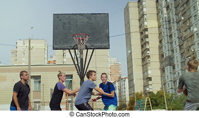 Teen streetball player missing a shot after assit and players fighting for rebound while playing basketball game on outdoor court. Active sporty teenagers playing streetball match on basketball court.