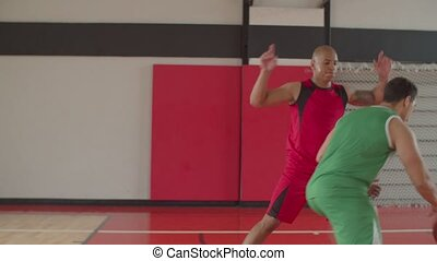 African american streetballer getting near hoop with dribbles, making a layup shot and failing to score field goal in game. Two basketball player playing half-court play on indoor basketball court.