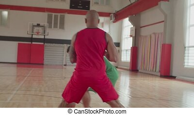 Streetballers playing one on one game indoors - Two athletic...