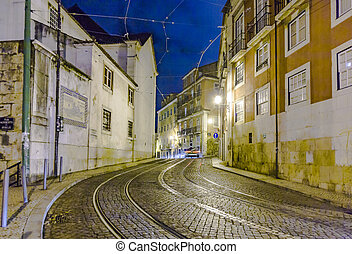 streetcar rails in the old part of Lisbon by night