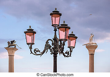 streetlight, St. Mark's Lion and St. Theodore's statue in the background, Venice, Italy