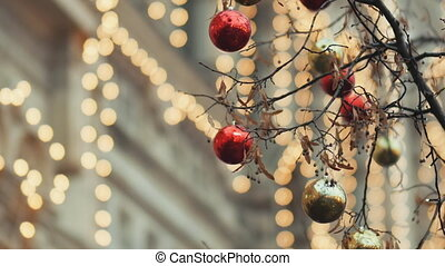 Streets fully decorated for Christmas with red and gold balls. Christmas tree in the city. House illuminated with a lot lights. New Year theme.