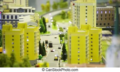 streets of toy small city with apartment houses, people in streets and park. Moving camera