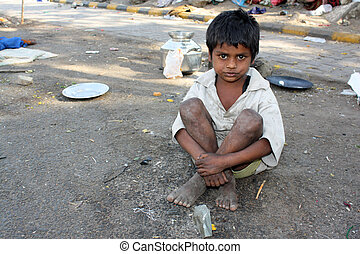 Streetside Indian Kid - A poor kid in India, sitting on the...