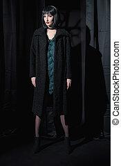 strega, moda, donna, nero portare, coat., standing, in, scuro, room.
