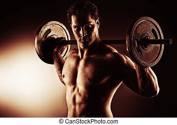 Portrait of a handsome bodybuilder posing over black background.