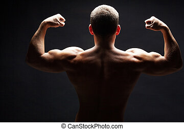 Strength - Back view of shirtless man demonstrating his...