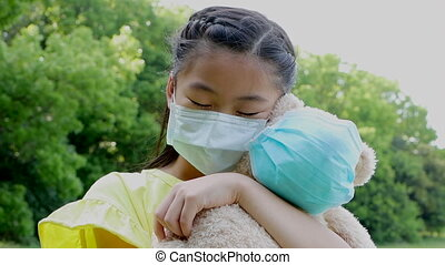 stress asian little girl holding toy bear wearing medical protective mask