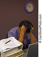 A man with his head down clenching his hair while working late into the night. He is surrounded by his computer & piles of documents, and the clock shows close to midnight.